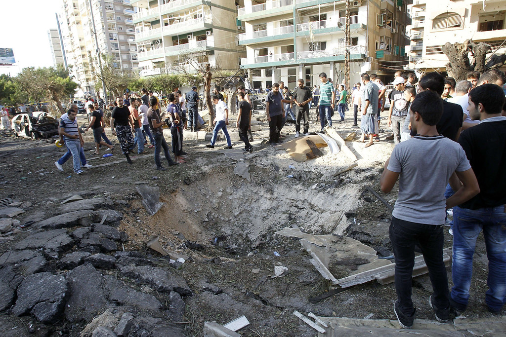 . Lebanese civilians gather next to a crater at the site of a blast outside the Al-Salam mosque in the northern city of Tripoli on August 23, 2013.  AFP PHOTO/ANWAR AMRO/AFP/Getty Images