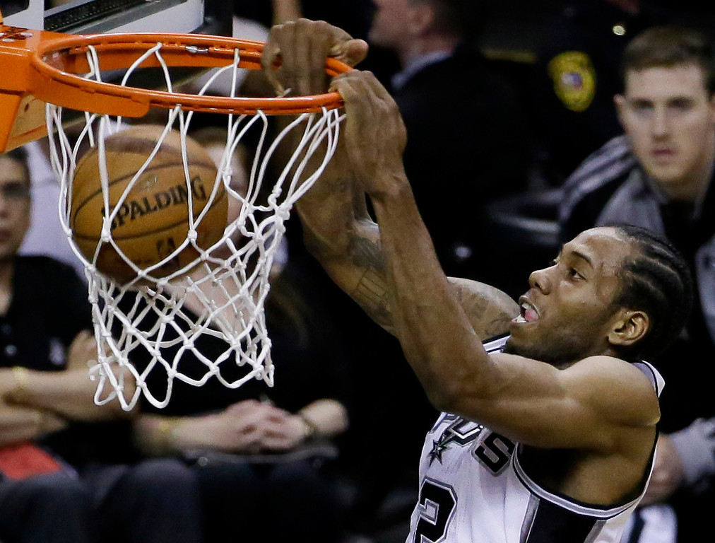 . San Antonio Spurs forward Kawhi Leonard (2) dunks against the Miami Heat during the first half in Game 5 of the NBA basketball finals on Sunday, June 15, 2014, in San Antonio. (AP Photo/Tony Gutierrez)