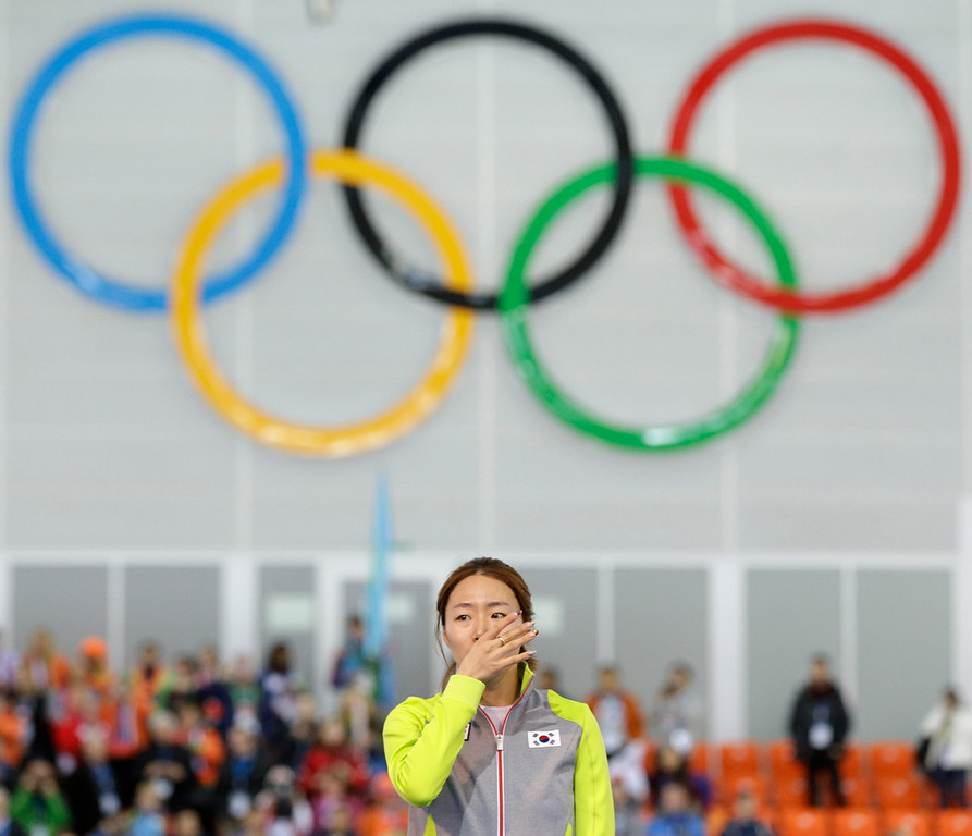 . Gold medalist South Korea\'s Lee Sang-hwa stands on the podium during the flower ceremony for the women\'s 500-meter speed skating race at the Adler Arena Skating Center during the 2014 Winter Olympics, Tuesday, Feb. 11, 2014, in Sochi, Russia. (AP Photo/Patrick Semansky)