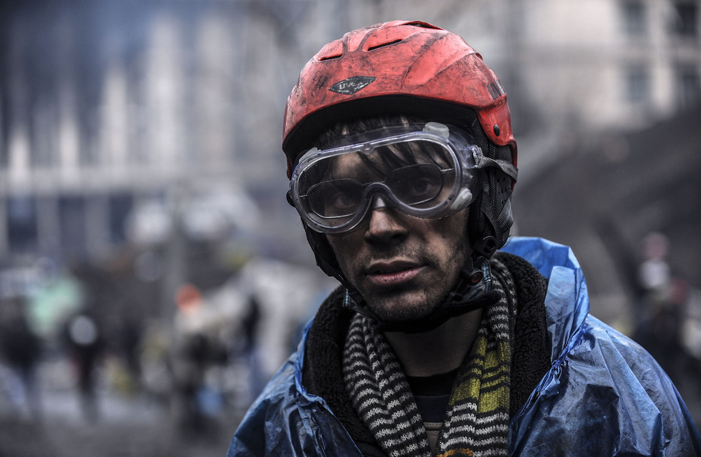 . A protestor stands near barricades during clashes with riot police in central Kiev on February 20, 2014 in Kiev. At least 25 protesters were killed on February 20 in fresh clashes between thousands of demonstrators and heavily-armed riot police in the heart of Kiev, AFP correspondents at the scene said. The bodies of eight demonstrators were lying outside Kiev\'s main post office on Independence Square, an AFP reporter said. AFP PHOTO/BULENT  KILIC/AFP/Getty Images