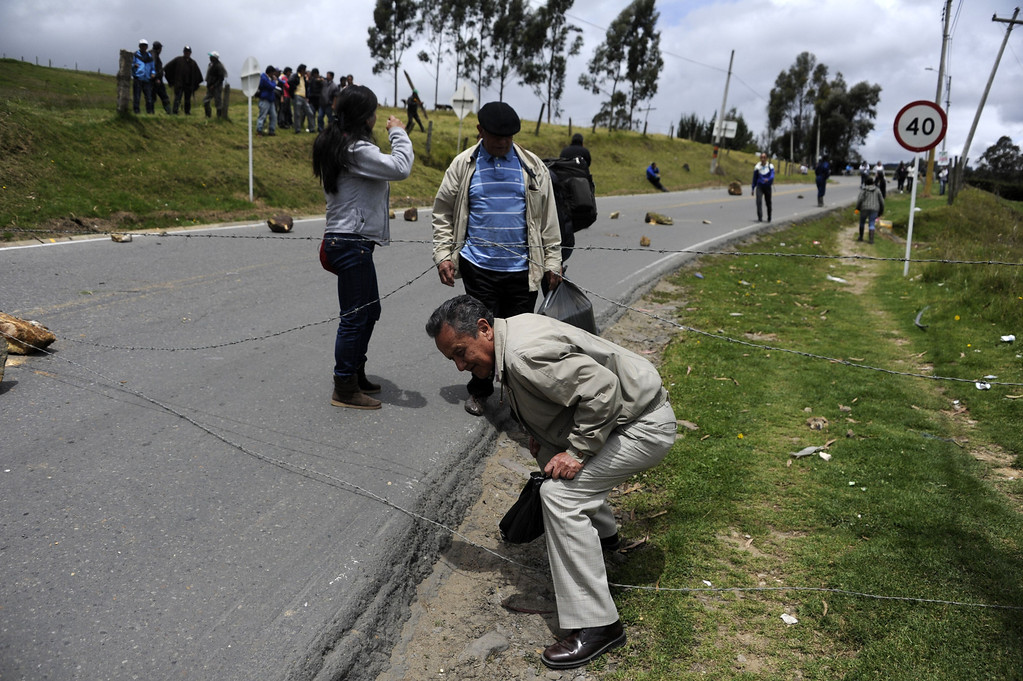 . People cross a road blockade by Colombian farmers demanding government subsidies and greater access to land, in La Calera, Cundinamarca department, on August 23, 2013. A five-day-old farmworkers\' protest in Colombia claimed its first fatality Friday when a man on a motorcycle crashed and died at a roadblock, police said Friday. Since the protests began Monday, farmworkers have closed roads at dozens of points in across the country, blocking the passage of cargo trucks and other vehicles from makeshift camps erected on sides of roads. EITAN ABRAMOVICH/AFP/Getty Images