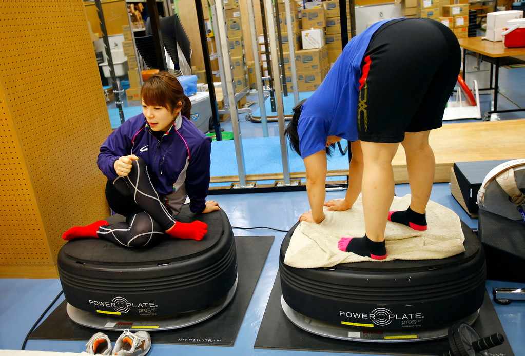 . In this Friday, Aug. 30, 2013 photo, Japanese weightlifter Hiromi Miyake, left, silver medalist in the London Olympic women\'s 48kg event, sits on a machine to warm up for muscle and body balance before her training at one of Tokyo\'s leading training centers. The Olympics are in Miyake\'s blood, a heritage that stretches back to the 1960s, when her uncle won a gold medal at the 1964 Tokyo Games and her father won bronze in Mexico City in 1968. With the Olympics coming to Tokyo in 2020, she hopes that will inspire the next generation of Japanese athletes. (AP Photo/Junji Kurokawa)