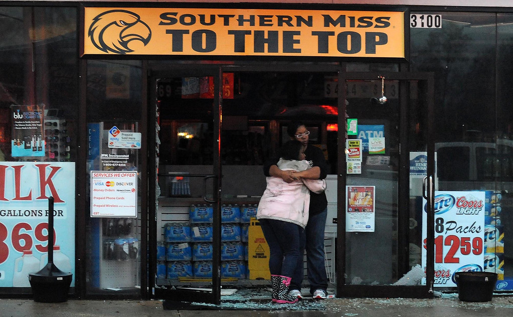 . Two people are seen consoling one another in a shattered door way along Hardy Street in Hattiesburg Miss., Feb 10, 2013 after a tornado passed through the city Sunday afternoon, Feb. 10, 2013. Major damage was reported in Hattiesburg and Petal, including on the campus of the University of Southern Mississippi. (AP Photo/The Hattiesburg American, Ryan Moore)