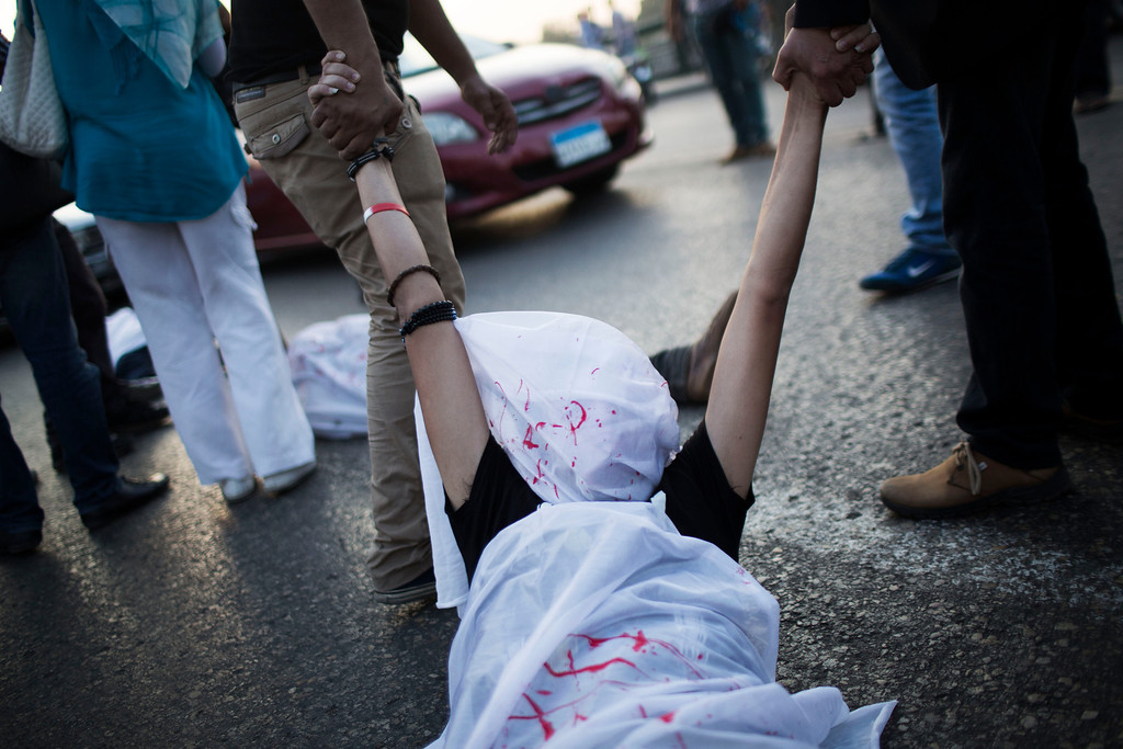 . Egyptian youths take a comrade covered with a fake blood-stained shroud while performing during a protest against the release of former Egypt\'s dictator Hosni Mubarak in Qasr Al-Nil bridge in downtown Cairo, Egypt, Thursday, Aug. 22, 2013. (AP Photo/Manu Brabo)