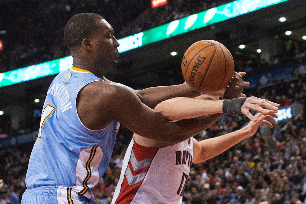 . Denver Nuggets\' Jordan Hamilton, left, and Toronto Raptors\' Jonas Valanciunas cross arms while vying for a rebound during the second half of an NBA basketball game in Toronto on Tuesday, Feb. 12, 2013. (AP Photo/The Canadian Press, Chris Young)