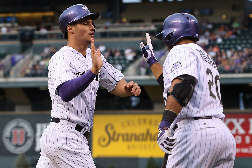 . DENVER, CO - MAY 02:  Nolan Arenado #28 of the Colorado Rockies scores on a double by Justin Morneau #33 of the Colorado Rockies and celebrates with Wilin Rosario #20 of the Colorado Rockies as the Rockies take a 2-1 lead over the New York Mets in the first inning at Coors Field on May 2, 2014 in Denver, Colorado.  (Photo by Doug Pensinger/Getty Images)