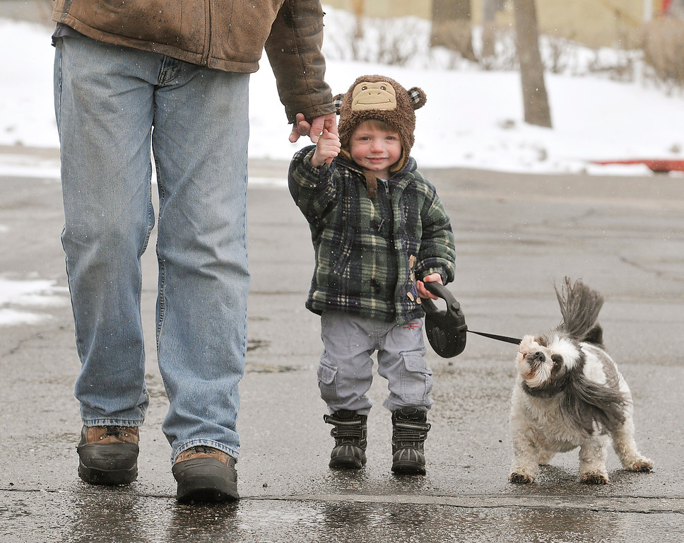 . Kirby Carlson, 19 months, holds his dad Steve\'s hand while walking his dog Allie Thursday April 18, 2013, in Virginia, Minn. Kirby was bundled up in his winter gear as another winter storm blew through the area bringing ice, snow and below freezing temperatures. (AP Photo/Mesabi Daily News, Mark Sauer)