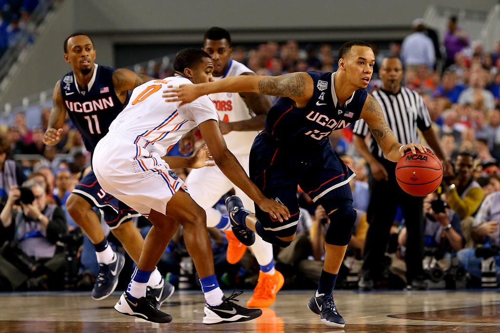 . ARLINGTON, TX - APRIL 05: Shabazz Napier #13 of the Connecticut Huskies brings the ball up the floor as Kasey Hill #0 of the Florida Gators defends during the NCAA Men\'s Final Four Semifinal at AT&T Stadium on April 5, 2014 in Arlington, Texas.  (Photo by Ronald Martinez/Getty Images)