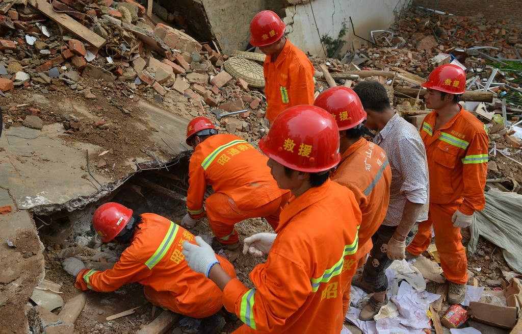 . Rescuers search for buried people at the quake-hit area on August 4, 2014 in Zhaotong, China. A 6.5-magnitude earthquake hit Zhaotong\'s Ludian county on August 3, killing at least 410 people.  (Photo by ChinaFotoPress/ChinaFotoPress via Getty Images)