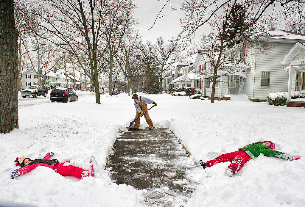 . Jason Smith  clears the sidewalk in front of his home at the 2400 block of Anthony Blvd., in Fort Wayne, Ind., before heading to work Wednesday morning March 6, 2013, as his daughters Kylie Smith, right, 8, and Alexa Smith, 7, make snow angels on their day off from school.  (AP Photo/The Journal Gazette, Swikar Patel)