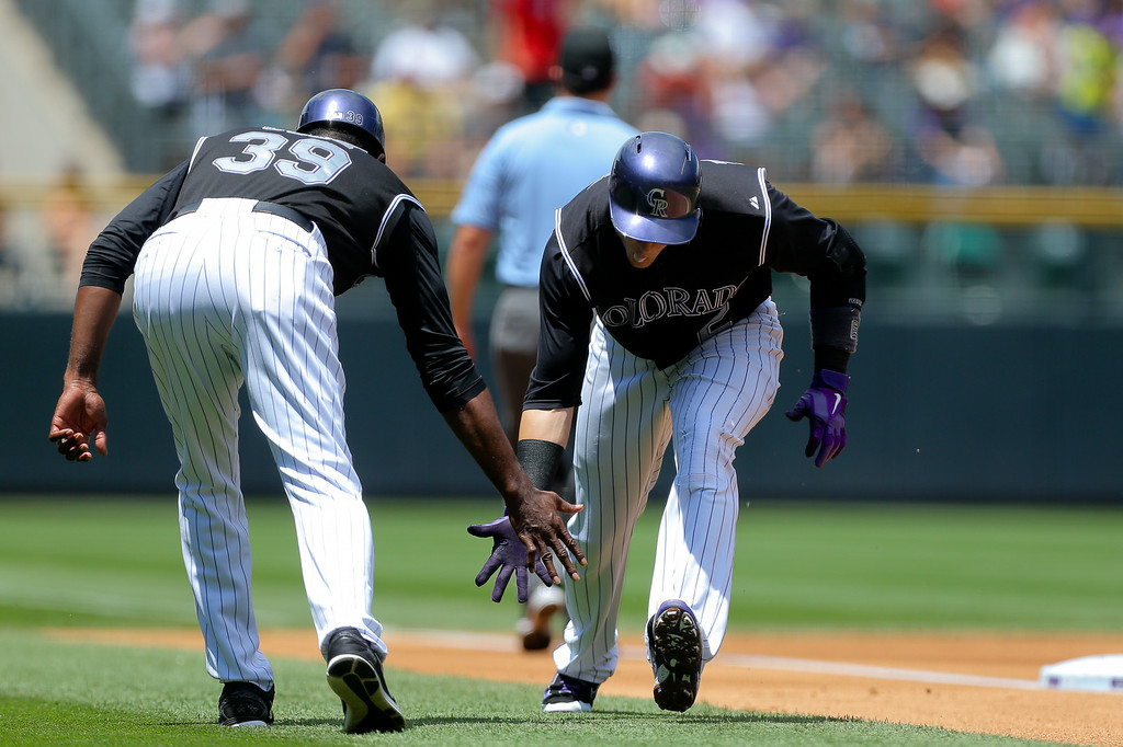 . DENVER, CO - JULY 9:  Troy Tulowitzki #2 of the Colorado Rockies is congratulated after hitting a solo home run by third base coach Stu Cole #39 during the first inning against the San Diego Padres at Coors Field on July 9, 2014 in Denver, Colorado. (Photo by Justin Edmonds/Getty Images)