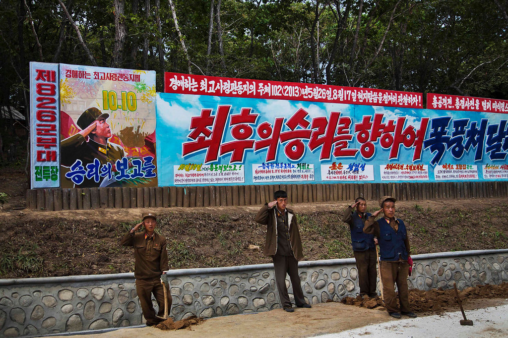 """. North Korean soldiers salute next to a propaganda billboard at a ski resort building project at North Korea\'s Masik Pass on Friday Sept. 20, 2013. The main text on the sign, in red, reads \""""To The Final Victory.\"""" North Korean authorities have been encouraging a broader interest in sports in the country, calling it \""""the hot wind of sports blowing through Korea.\"""" (AP Photo/David Guttenfelder)"""