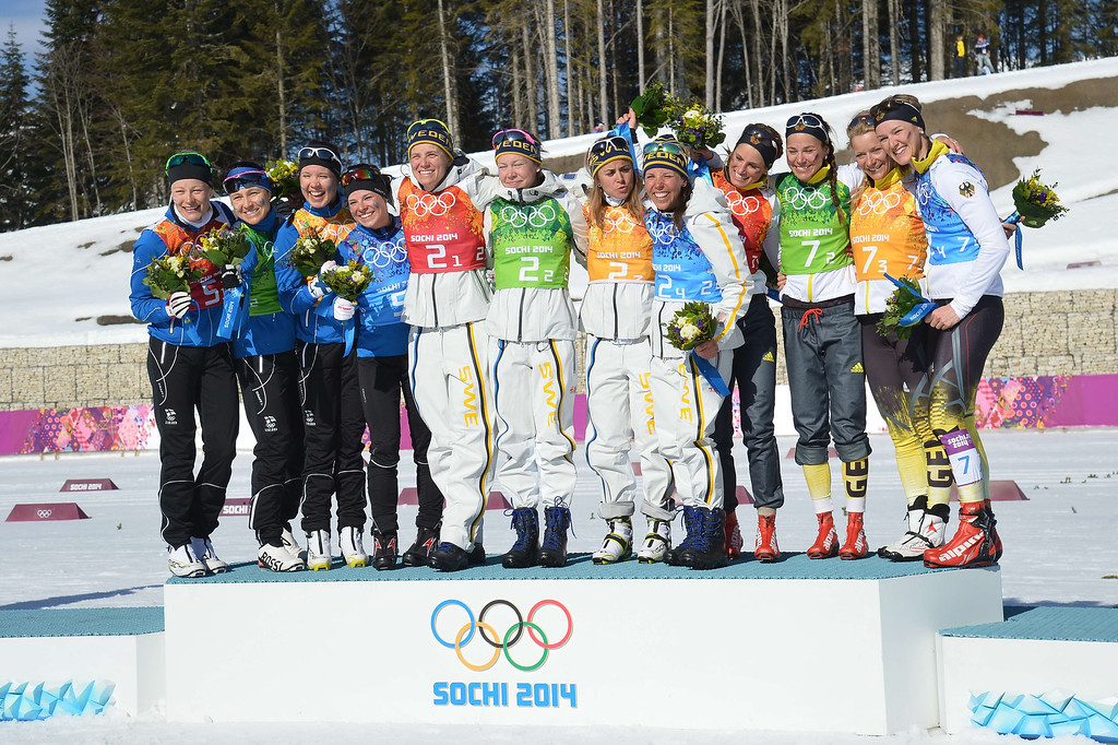 . (L-R) Silver Medallist, Finland; Gold Medallist, Sweden; and Bronze Medallist, Germany celebrate on the podium during the Women\'s Cross-Country Skiing 4x5km Relay Flower Ceremony at the Laura Cross-Country Ski and Biathlon Center during the Sochi Winter Olympics on February 15, 2014, in Rosa Khutor near Sochi. ALBERTO PIZZOLI/AFP/Getty Images