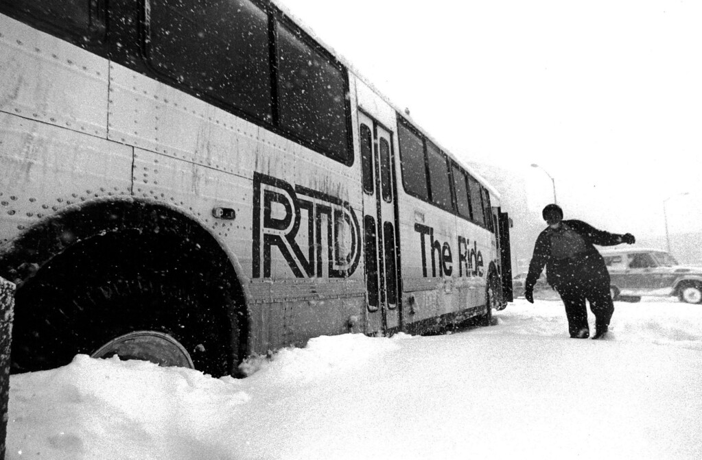 . A man wades through the snow next to a stuck bus during the Blizzard of \'82. Denver Post Library Archive