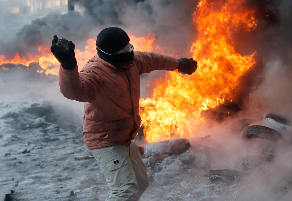 . A protester throws a stone against riot police during a clash in central Kiev, Ukraine, Saturday, Jan. 25, 2014. Ukraine\'s Interior Ministry has accused protesters in Kiev of capturing two of its officers as violent clashes have resumed in the capital and anti-government riots spread across Ukraine. (AP Photo/Efrem Lukatsky)