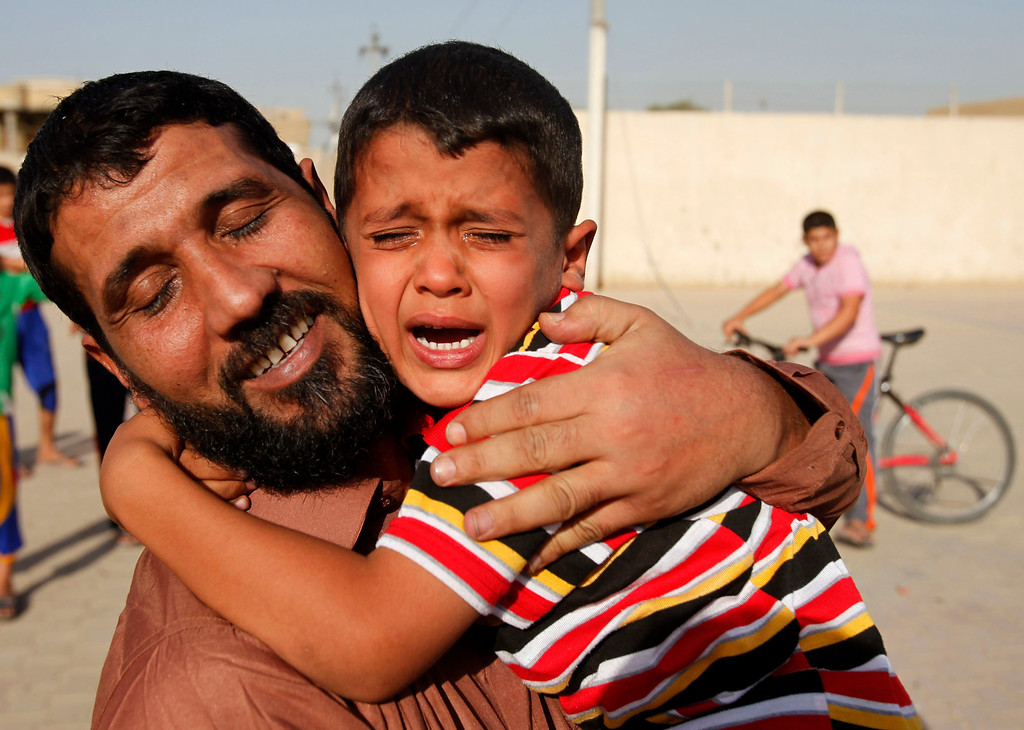 . Haidar Talib embraces his four-year-old son Mustafa as he is released from U.S. military custody in Baghdad, Iraq, Sunday, Sept. 27, 2009. He was among 37 members of a militant group called Asaib Ahl al-Haq, or League of the Righteous, who were released. The group was allegedly involved in kidnapping of five British contractors in Baghdad in 2007. (AP Photo/Khalid Mohammed)