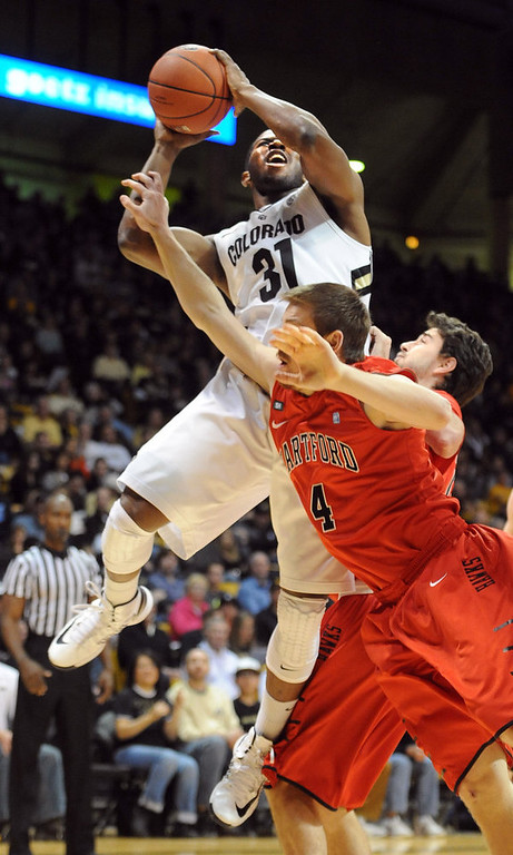 . Jeremy Adams of CU goes to the basket on Corban Wroe of Hartford, during the first half of the December 29, 2012 game in Boulder. (Cliff Grassmick / Daily Camera) December 29, 2012
