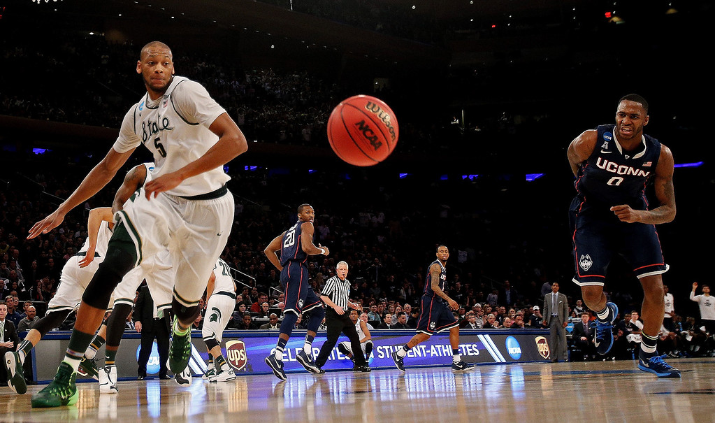 . Adreian Payne #5 of the Michigan State Spartans and Phillip Nolan #0 of the Connecticut Huskies chase after a loose ball during the East Regional Final of the 2014 NCAA Men\'s Basketball Tournament at Madison Square Garden on March 30, 2014 in New York City.  (Photo by Bruce Bennett/Getty Images)