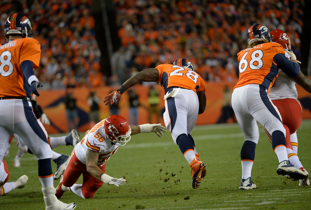 . Denver Broncos running back Montee Ball (28) breaks through a hole in the first quarter. The Denver Broncos take on the Kansas City Chiefs at Sports Authority Field at Mile High in Denver on November 17, 2013. (Photo by Joe Amon/The Denver Post)