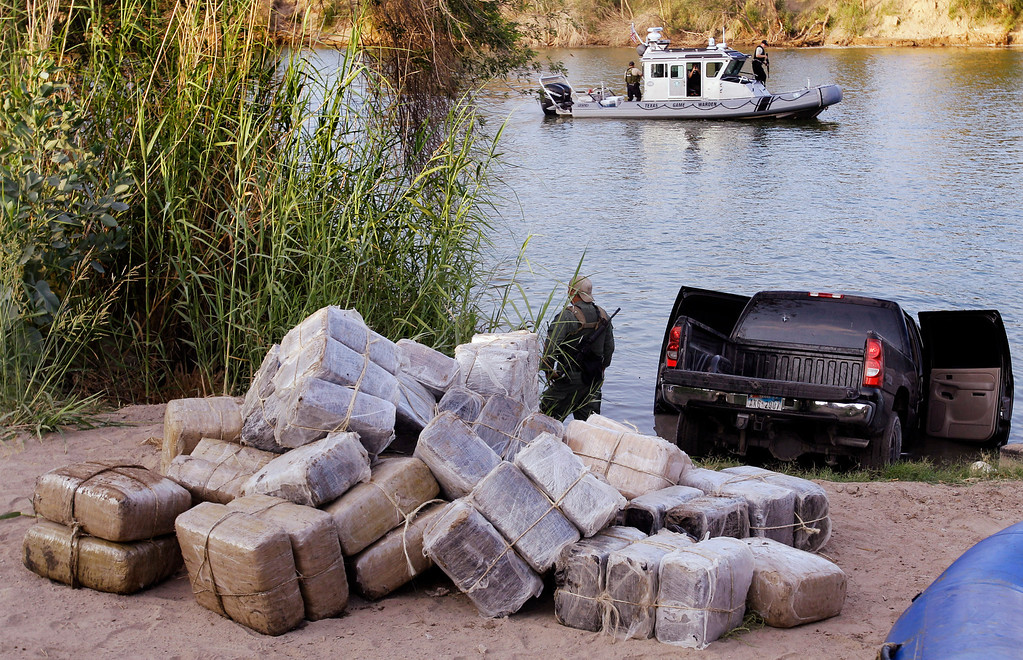 . In this June 8, 2011, file photo U.S. Customs and Border Patrol and Texas Department of Public Safety seize 57 bundles of marijuana weighing more than 1,200 pound at the Texas border along the Rio Grande in Abram, Texas. Most illegal border crossers are apprehended along the 2,000-mile long Mexican border in California, Arizona, New Mexico, and Texas. In the budget year that ended in September, 18,506 agents on that border made a combined 327,577 apprehensions, an average of nearly 18 apprehensions per agent, and spent about $283 million on overtime an according to Associated Press analysis of agency records. (AP Photo/Eric Gay, File)