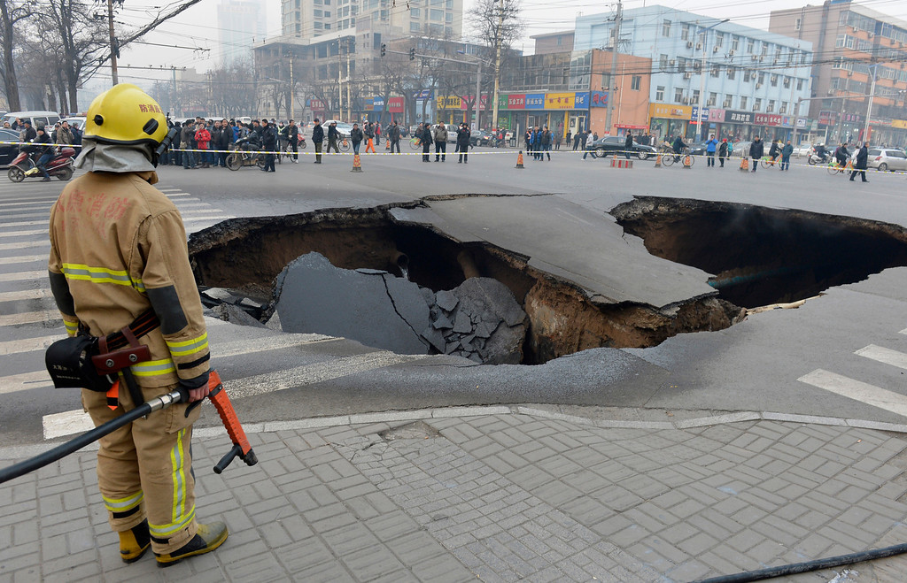 . A firefighter stands next to a cave-in at a crossroad in Taiyuan, Shanxi province, December 26, 2012. The cause of the cave-in, measuring about 6 meters (20 ft.) in depth, 10 meters (32.8 ft.) in diameter, is still under investigation. Three coal gas tubes and one water tube were broken during the collapse and firefighters are trying to dilute the coal gas at the site, reported local media. REUTERS/Stringer