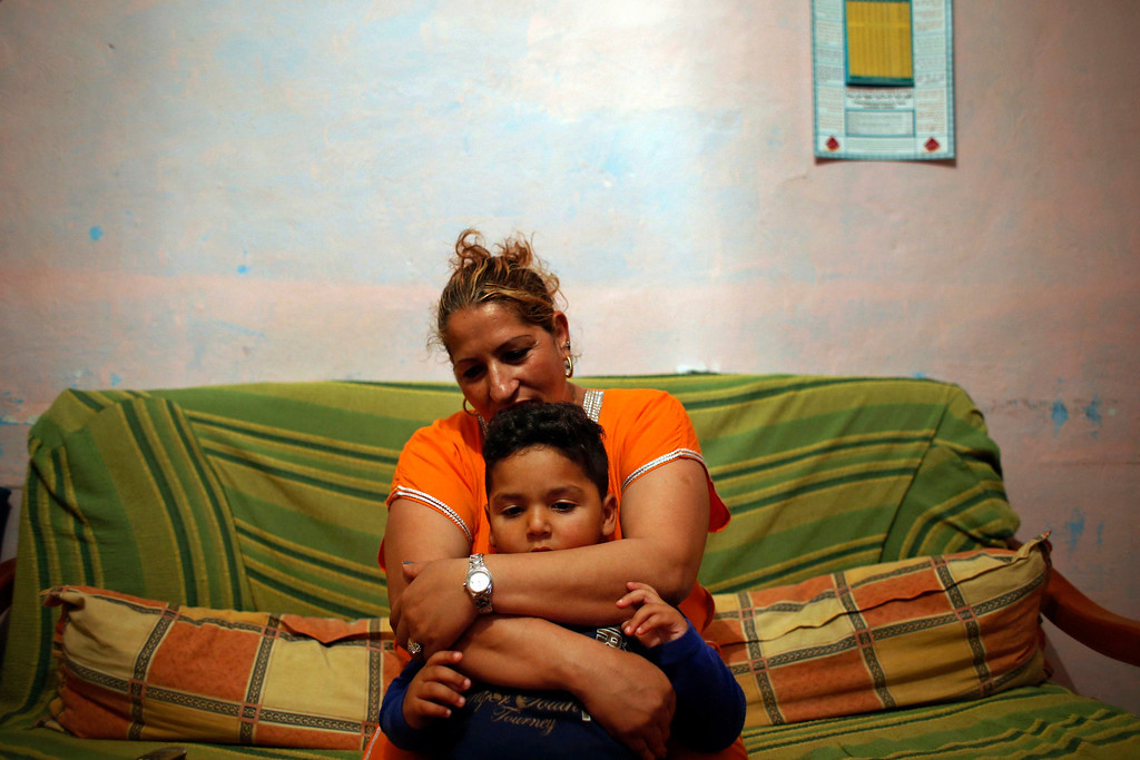 . Farm worker Mustapha El-Mezroui\'s wife, Mahjouba, embraces their three-year-old son Bilal, in the living room of their home on a farm belonging to Spanish farmer Santiago Perez in the southern Spanish region of Murcia June 5, 2013.  El-Mezroui left his native Morocco for Spain on a makeshift boat in the mid-1990s, and now works as a keeper and farm hand on a farm outside La Puebla, Cartagena, where he lives with his wife and three-year-old son. He supervises day labourers, does maintenance work and performs other jobs, helping to keep the farm secure. The majority of day labourers in the region come from Morocco and Ecuador, and it can be rare to see Spanish labourers in the fields. Nevertheless, as Spain wrestles with economic crisis and youth unemployment levels above 50 percent, some young Spaniards are starting to consider the kinds of jobs mostly performed by immigrants during the boom years. Picture taken June 5, 2013. REUTERS/Susana Vera