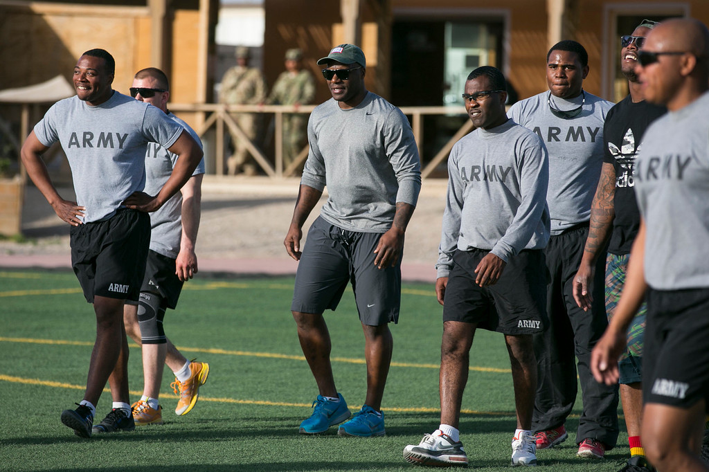 . Cleveland Browns linebacker D�Qwell Jackson (3rd L) and Denver Broncos linebacker Von Miller (2nd R partly blocked) encourage their service member teammates during an impromptu touch football game with troops stationed in the Middle East on a stop of their the week-long USO/NFL tour March 16, 2013.  USO Photo by Fred Greaves
