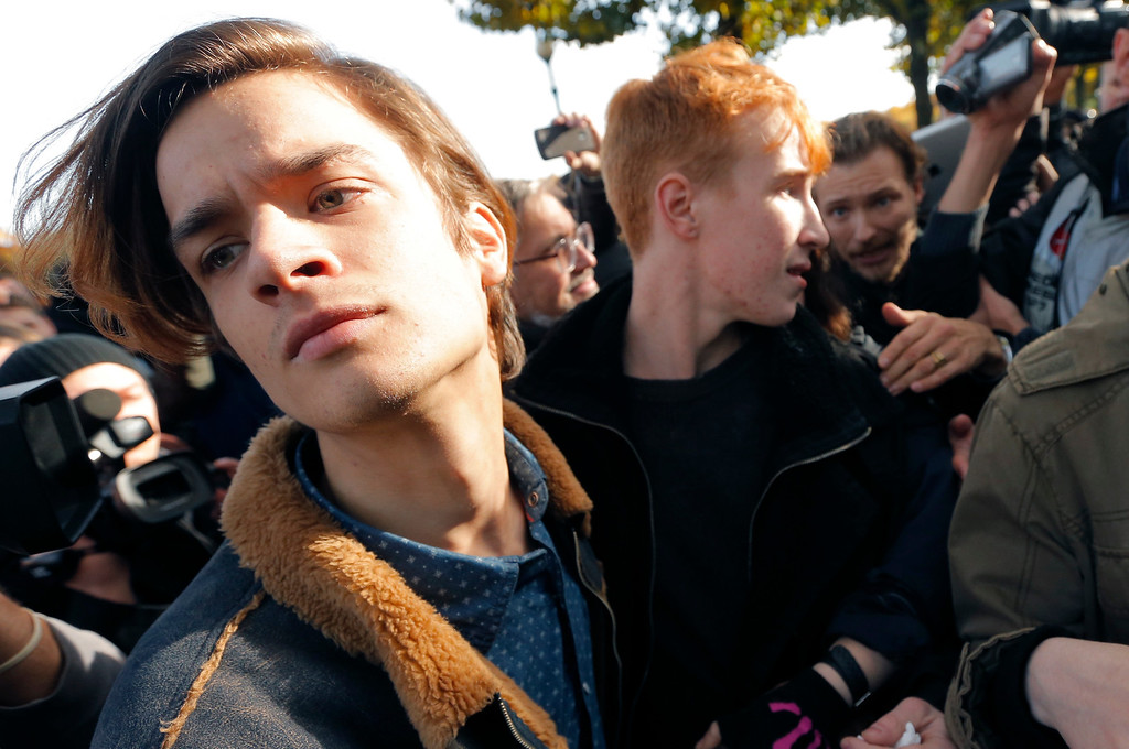 . Gay rights activists, left, argue with anti-gay protesters during an authorized gay rights rally in St. Petersburg, Russia, Saturday, Oct. 12, 2013. A gay rights rally in St. Petersburg has ended in scuffles after several dozen protesters were confronted by about 200 conservative and religious activists. The police standing nearby waited until clashes broke out between the two groups before intervening. According to Russian news agencies, the police detained 67 people from both sides. (AP Photo/Dmitry Lovetsky)