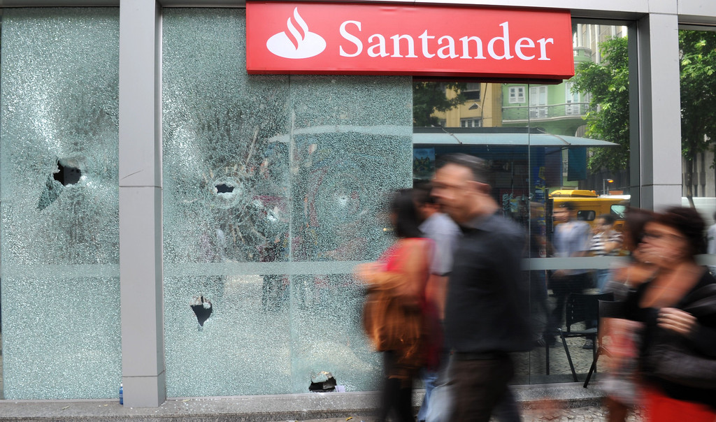 . pedestrians pass by a bank whose windows were broken during a protest overnight in downtown Rio de Janeiro, Brazil, on June 21, 2013.  AFP PHOTO / TASSO  MARCELO/AFP/Getty Images