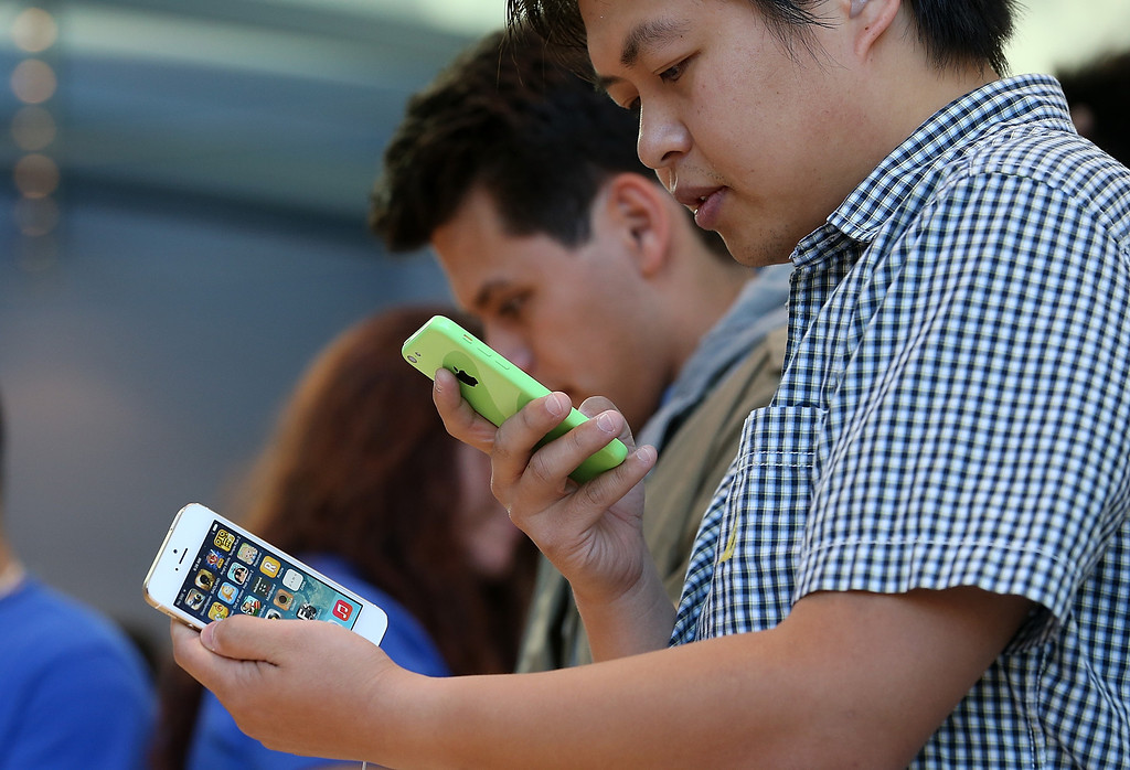 . An Apple Store customer looks at the new Apple iPhone 5C and 5S at an Apple Store on September 20, 2013 in Palo Alto, California.   (Photo by Justin Sullivan/Getty Images)