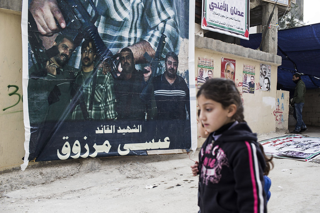 . Children walk past hanging posters of Adnan Al-Afandi who served 23 years in Israeli Prison and is expected to be released tonight as part of the 26 prisoners that will be released as part of terms of the renewed U.S. brokered peace talks on December 30, 2013 in Bethlehem, West Bank.  (Photo by Ilia Yefimovich/Getty Images)