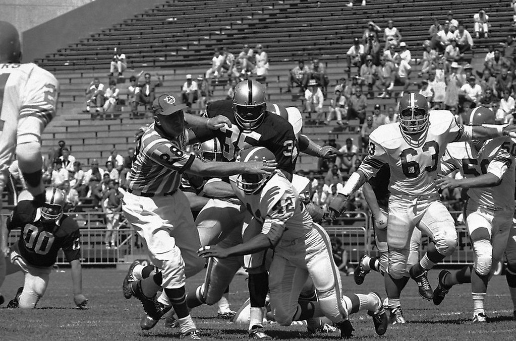 . Umpire Al Huetter (28) was about to be tackled in this second quarter action between Oakland Raiders and Denver Broncos at Oakland Coliseum, Sunday, Sept. 11, 1967. Huetter managed to get out of the way charging back Hewritt Dixon (35) who gained 10 on this pass play. Bronco in foreground is Lonnie Wright (42). Oakland won, 51-0. (AP Photo/Sal Veder)
