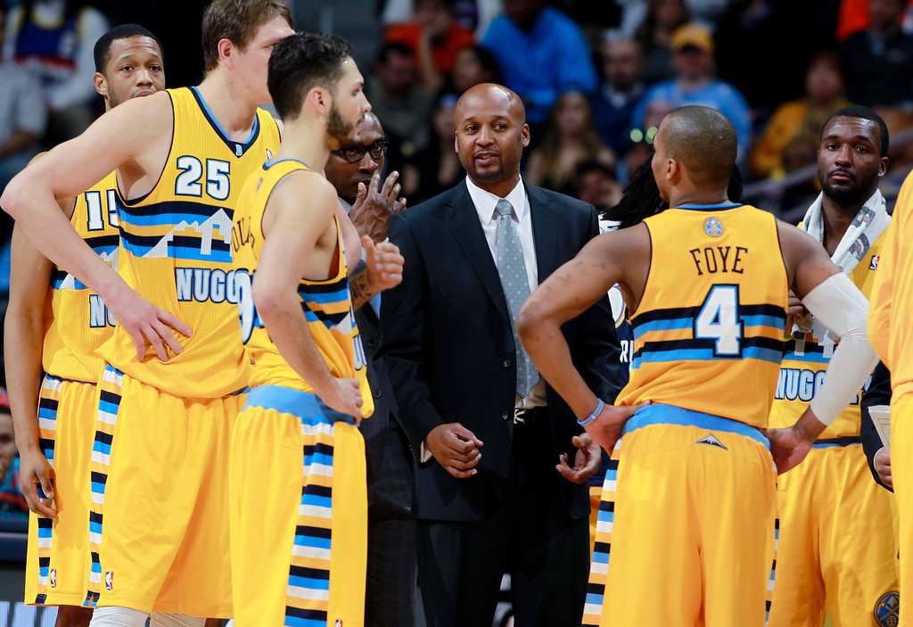 . Denver Nuggets coach Brian Shaw, center, confers with players during a timeout against the Toronto Raptors in the fourth quarter of the Raptors\' 100-90 victory in an NBA basketball game in Denver on Friday, Jan. 31, 2014. (AP Photo/David Zalubowski)