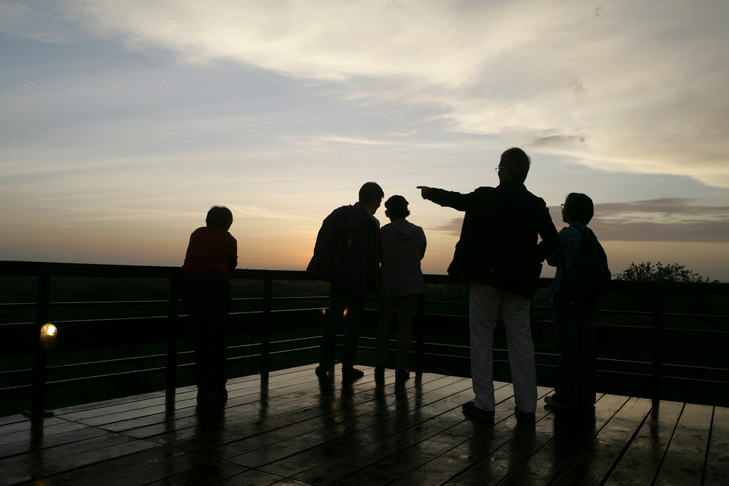 . Tourists watch the sunrise from the deck of Seronera Lodge in Serengeti National Park, Tanzania, Africa.