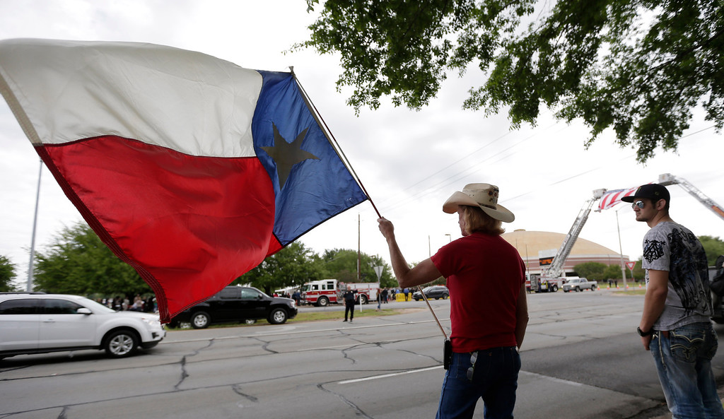 . Mark Turner holds a Texas flag as he wait for a procession to pass prior to a memorial service for first responders who died in last week\'s fertilizer plant explosion in West, Texas, Thursday, April 25, 2013, in Waco, Texas. (AP Photo/Eric Gay)