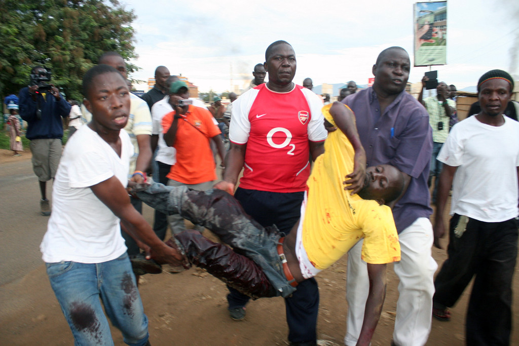 . A protester is helped by others after he was shot by police in Kondele, Kisumu, Saturday, March 30, 2013 after Supreme Court declared President elect Uhuru Kenyatta as the fourth president of the Republic of Kenya.(AP Photo/James Kaii)