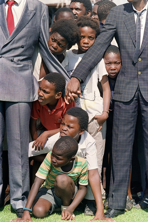 . Young boys try to see ANC President Nelson Mandela at Orlando soccer stadium 12 February 1990 whilst thousands of Sowetans wait for him. Mandela arrived in Johannesburg this evening but has not been to Soweto yet. (Photo credit should read ALEXANDER JOE/AFP/Getty Images)