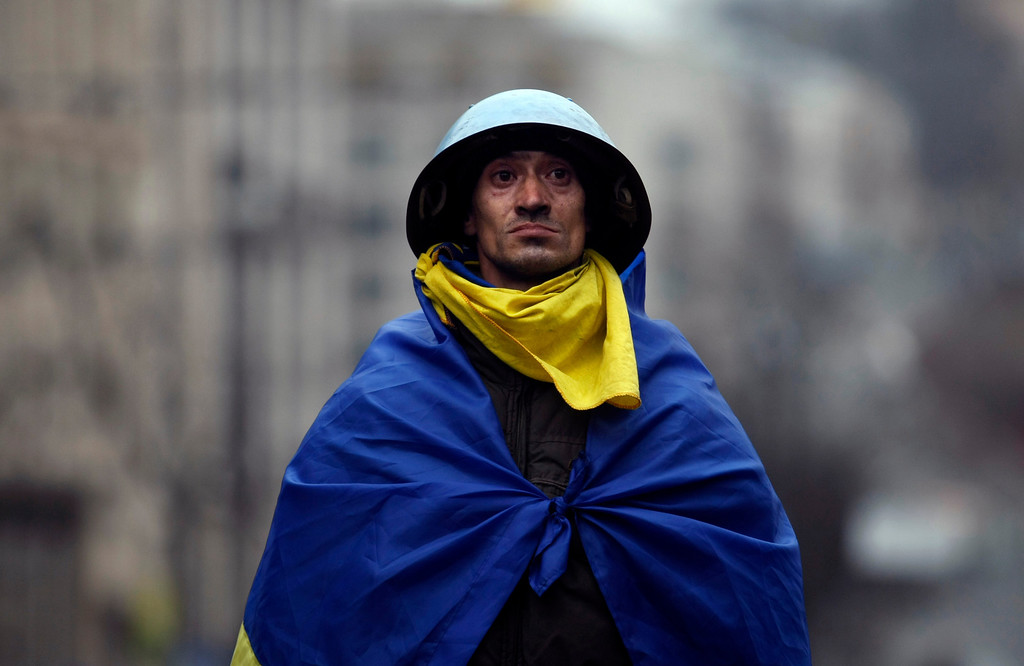 . An anti-government protester draped in a Ukrainian flag stands atop a barricade on the outskirts of Independence Square in Kiev, Ukraine, Thursday, Feb. 20, 2014. (AP Photo/Marko Drobnjakovic)