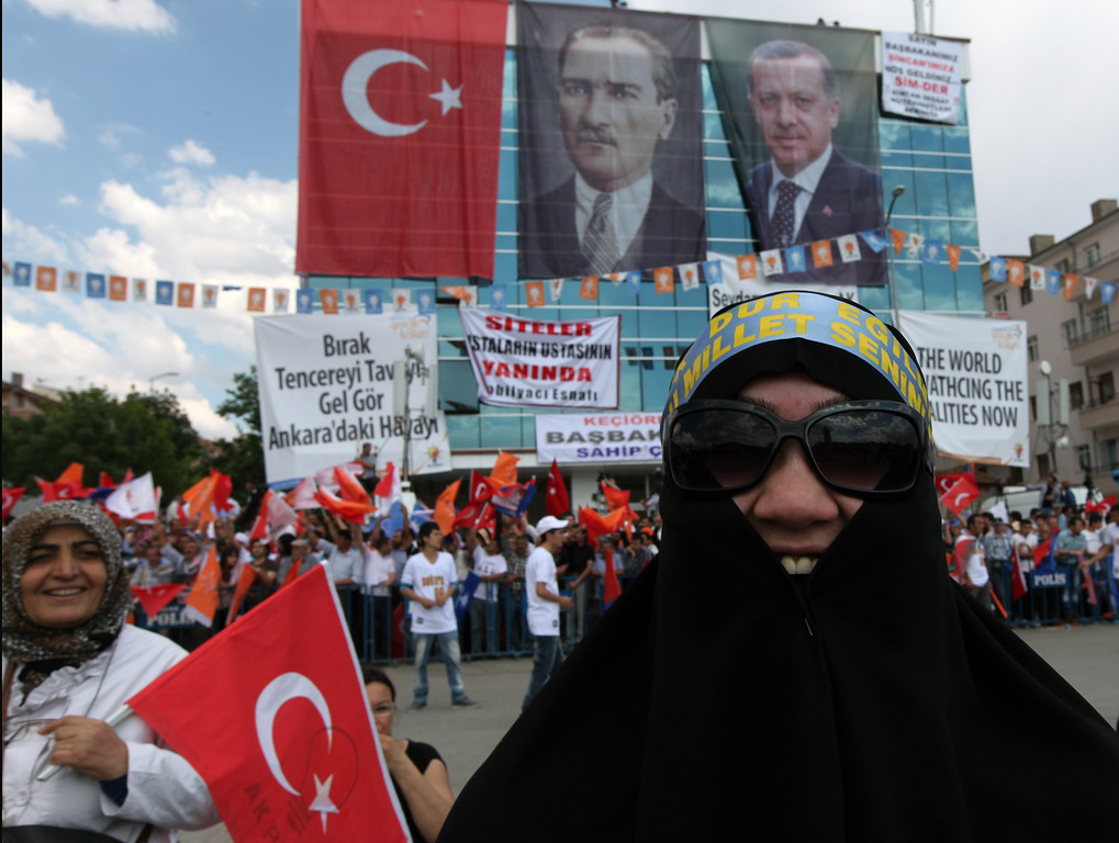 . Supporters of Turkish Prime Minister Recep Tayyip Erdogan wave flags before he arrives to address a party rally outside Ankara, Turkey, Saturday, June 15, 2013.  Erdogan said Friday he has asked a small delegation of protesters to convince those occupying a park to withdraw, adding that he is hopeful their protest action would end soon. (AP Photo/Burhan Ozbilici)