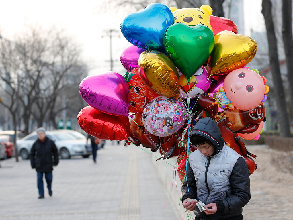 . A youth selling balloons counts money on Valentine\'s Day at a shopping district in Beijing February 14, 2013. REUTERS/Kim Kyung-Hoon