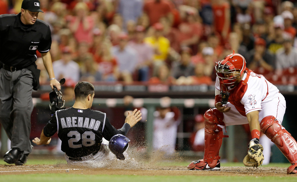 . Colorado Rockies\' Nolan Arenado (28) scores on a double hit by Justin Morneau in the ninth inning of a baseball game against the Cincinnati Reds, Friday, May 9, 2014, in Cincinnati. Reds\' Brayan Pena, right, catches as umpire Cory Blaser makes the call. Cincinnati won 4-3. (AP Photo/Al Behrman)