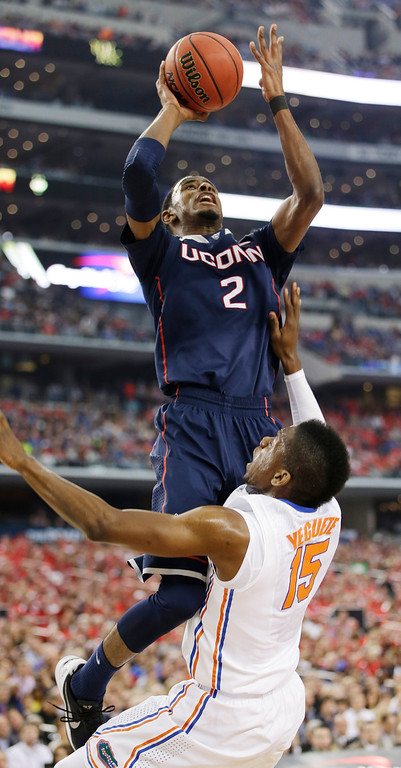 . Connecticut forward DeAndre Daniels (2) shoots over Florida forward Will Yeguete (15) during the first half of the NCAA Final Four tournament college basketball semifinal game Saturday, April 5, 2014, in Arlington, Texas. (AP Photo/David J. Phillip)