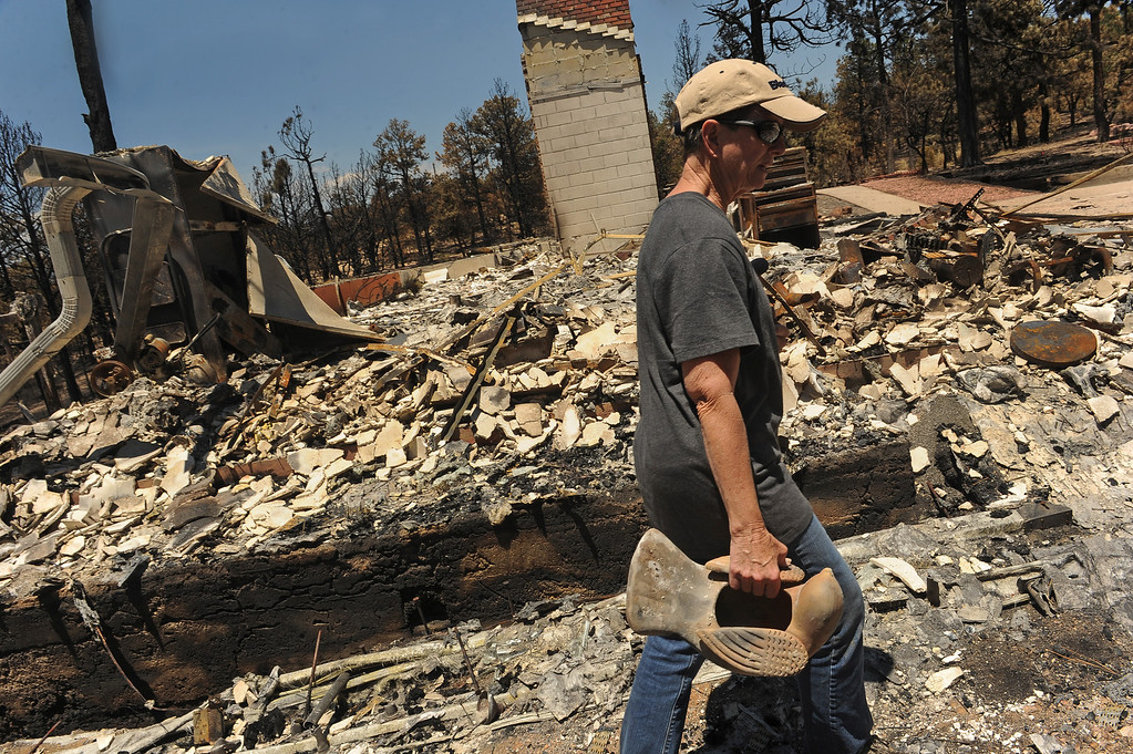 . BLACK FOREST, CO - JUNE 19:  Cindy Mitchell carries a ceramic bird that she recovered from the ashes of her home on Darr Drive in Black Forest, CO on June 19, 2013.   Cindy and Ray Mitchell came home for the first time since the fire in Black Forest, CO on June 19, 2013.  Her husband Ray had seen the fire coming almost immediately as it had started just southwest of their home. Their\'s was one of the first houses to burn.  The couple had lived in the home for over 22 years and were even married on the property.  The Black Forest Fire stands at 85% containment and more and more homeowners are being allowed back into their homes for a few hours each day. 14, 280 acres have burned and the total number of homes lost increased to 509.  Photo by Helen H. Richardson/The Denver Post)