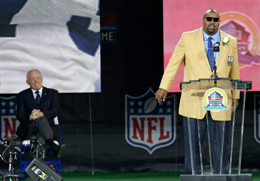 . Former NFL football player Larry Allen, right, speaks during the induction ceremony as presenter Dallas Cowboys owner Jerry Jones, left, smiles at the Pro Football Hall of Fame Saturday, Aug. 3, 2013, in Canton, Ohio. (AP Photo/Tony Dejak)