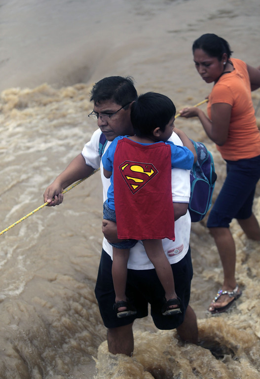 . Residents  wade through a flooded street in Acapulco, Guerrero state, Mexico, on September 17, 2013 as heavy rains hit the country. Mexican authorities scrambled Tuesday to launch an air lift to evacuate tens of thousands of tourists stranded amid floods in the resort of Acapulco following a pair of deadly storms. The official death toll rose to 47 after the tropical storms, Ingrid and Manuel, swarmed large swaths of the country during a three-day holiday weekend, sparking landslides and causing rivers to overflow in several states. Pedro PARDO/AFP/Getty Images