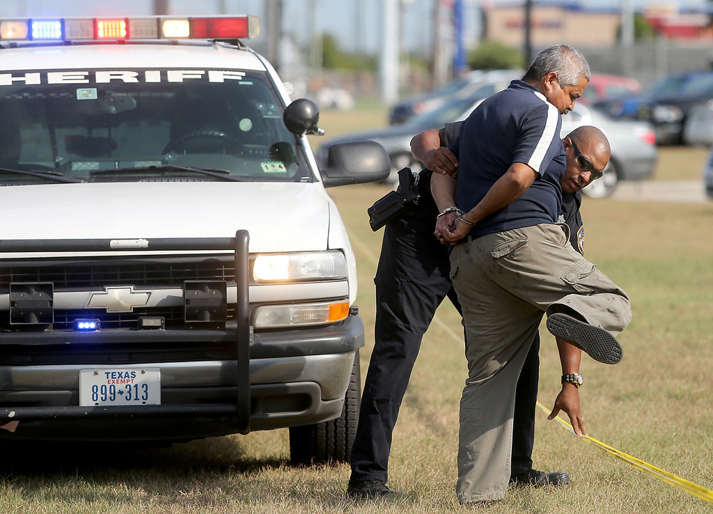 . A Harris County Sheriff takes a person into custody on the grounds of Spring High School September 4, 2013 in Spring, Texas.  (Photo by Thomas B. Shea/Getty Images)