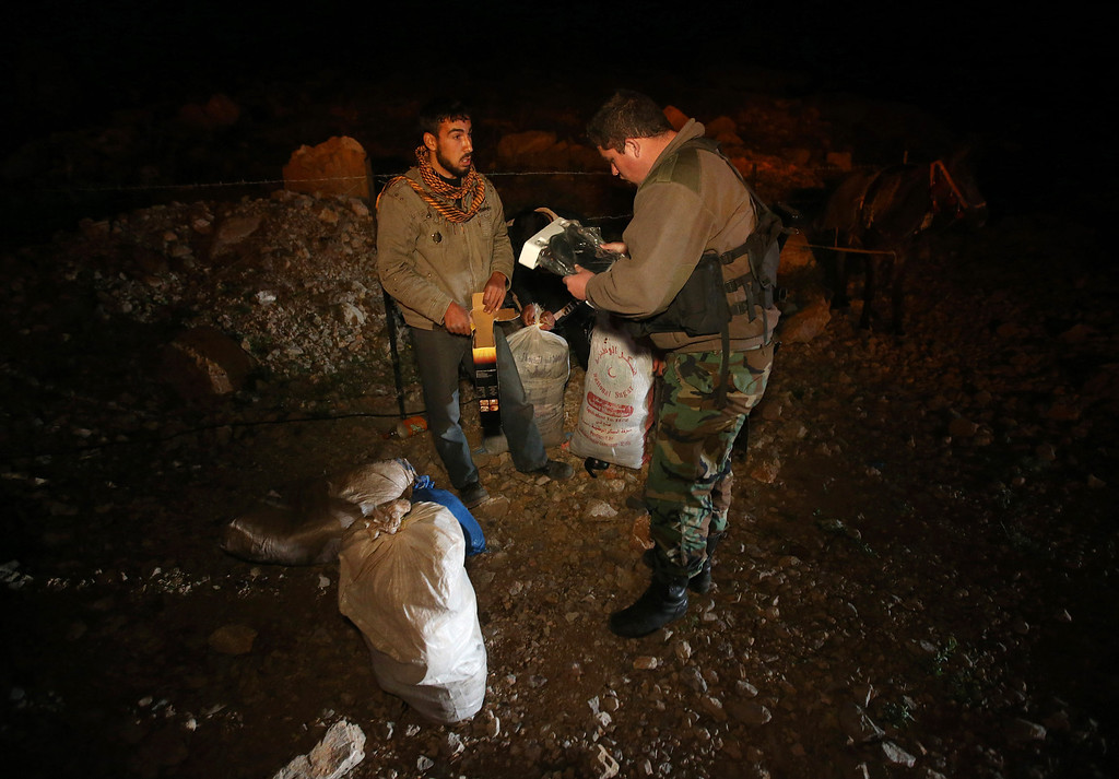 . In this picture taken on early Sunday, April 20, 2014, a Lebanese army soldier searches the belongings of a Syrian man who fled from the village of Beit Jinn near the Israeli-occupied Golan Heights, after he descended from the 2,814-meter (9,232-foot) Mount Hermon (Jabal el-Sheikh), into the town of Chebaa in southeast Lebanon. The soldiers are particularly suspicious of young men, like 28-year-old Saleh Zawaraa, who was wrapped in bandages. He told the soldiers he was not a fighter, but was hit by a tank shell outside of Beit Jinn while trying to bring bread into the village. The soldiers let him through.(AP Photo/Hussein Malla)