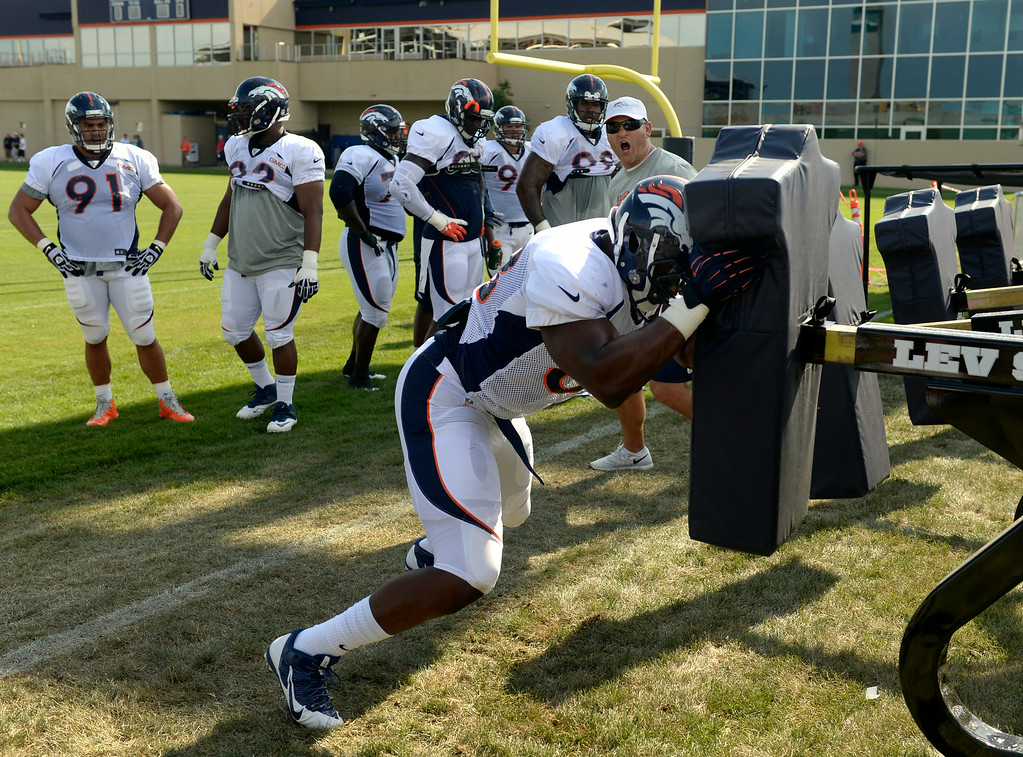 . Kenny Anunike (68) runs through drills on Saturday. The Denver Broncos football team hold their workouts for the team during mini-camp at Dove Valley in Centennial on Saturday, July 26, 2014. (Photo by Kathryn Scott Osler/The Denver Post)