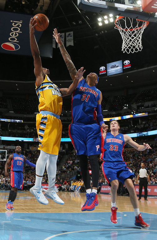 . Denver Nuggets forward Darrell Arthur, left, goes up for shot over Detroit Pistons forward Charlie Villanueva as Pistons forward Jonas Jerebko, back, of Sweden, comes in to cover in the fourth quarter of the Nuggets\' 118-109 victory in an NBA basketball game in Denver on Wednesday, March 19, 2014. (AP Photo/David Zalubowski)