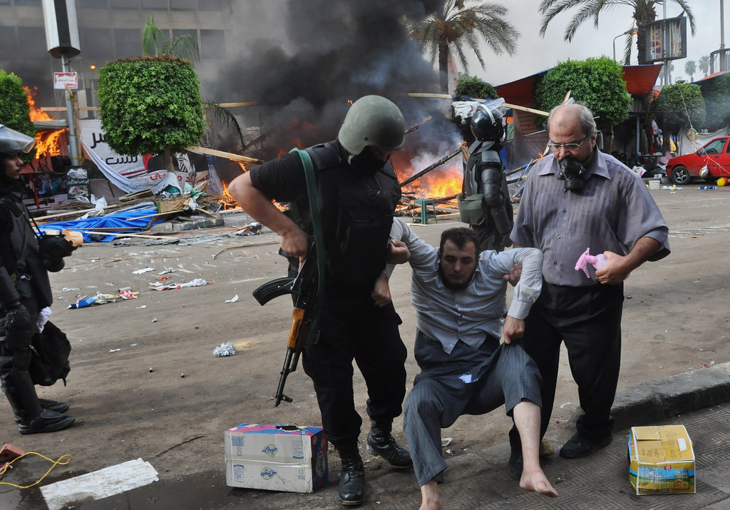 . An Egyptian security force and a man carry a protester as security forces clear a sit-in camp set up by supporters of ousted Islamist President Mohammed Morsi near Cairo University in Cairo\'s Giza district, Egypt, Wednesday, Aug. 14, 2013.  (AP Photo/Hussein Tallal)